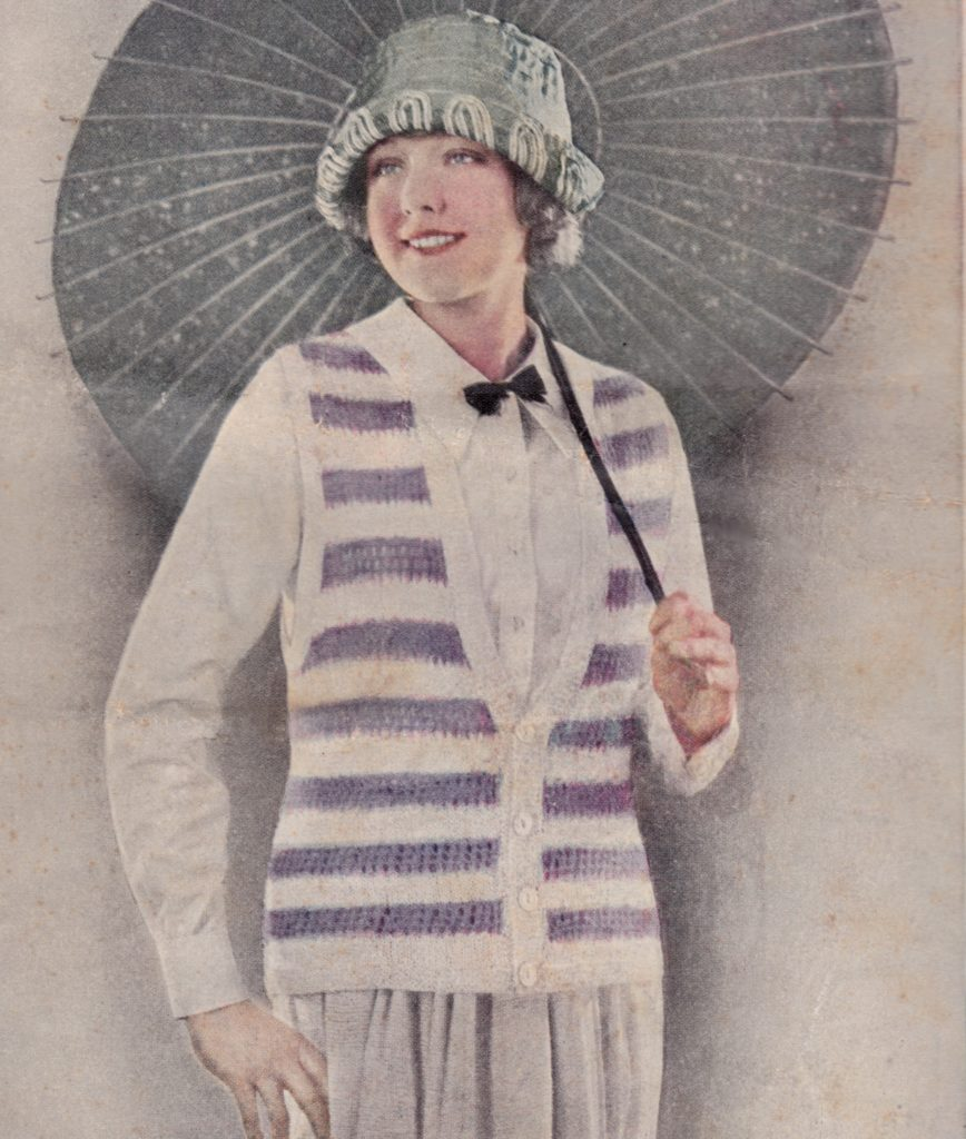 Fashion illustration of woman in knitted outfit with hat and umbrella, wearing a striped blue and wite sleeveless cardigan over a white blouse and matching skirt with black bow tie.