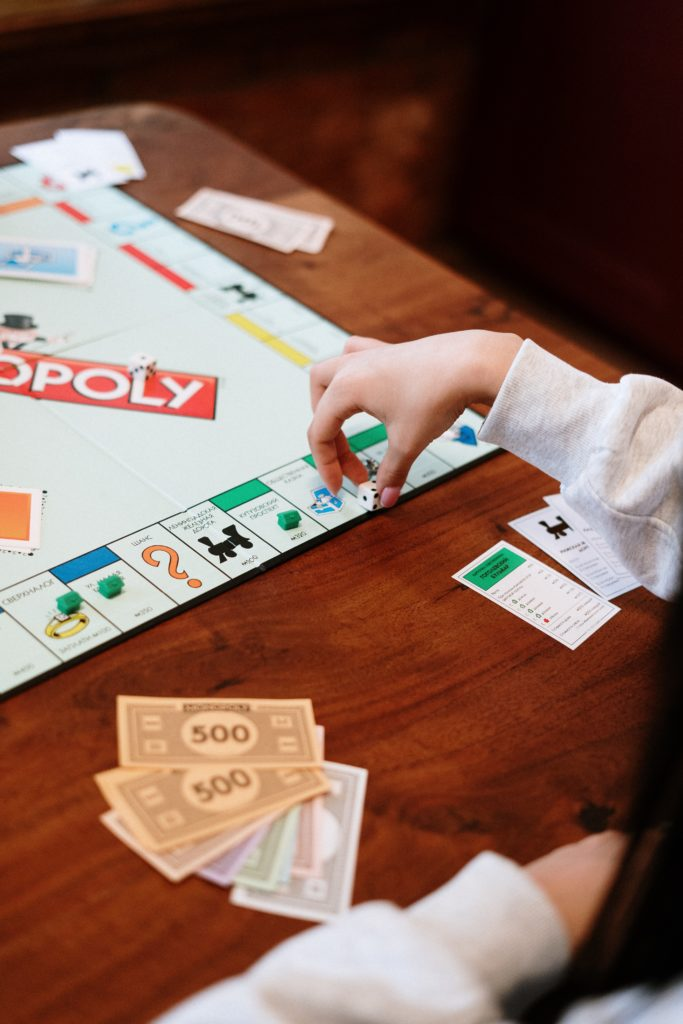 To show the Monopoly board game being played.