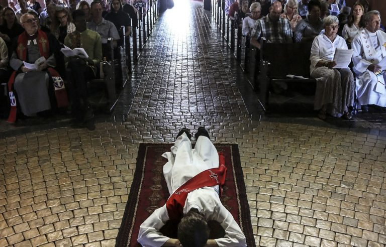 A woman about to be ordained as a priest lies prostrate