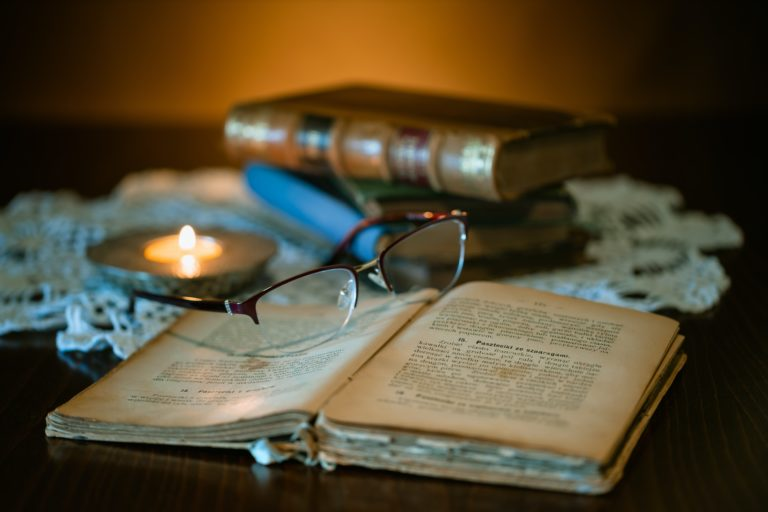 Table wiith old books and tealight on cloth. Spectacles lying on open book in front.