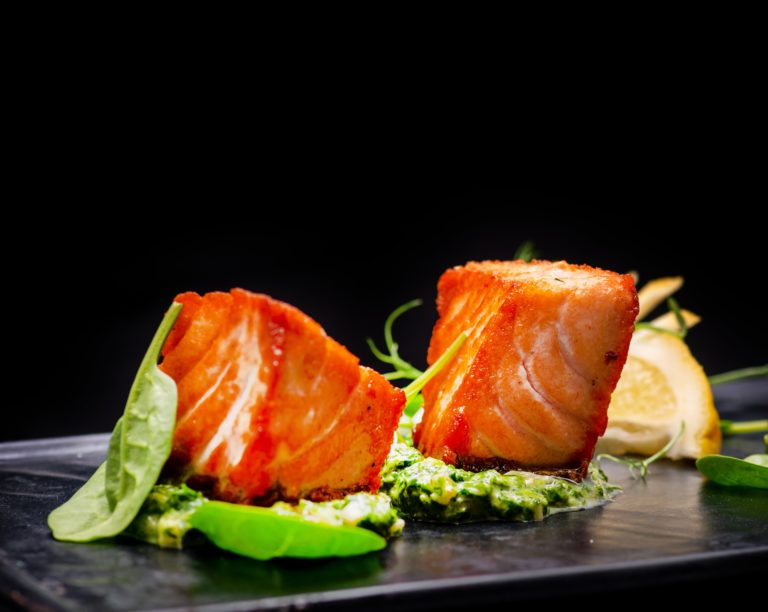 Fish with wasabi and trimmings on black plate with black background
