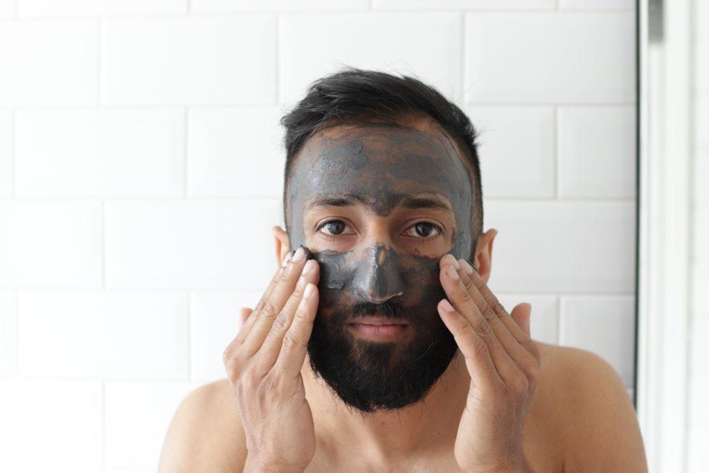 Man applying charcoal facemask