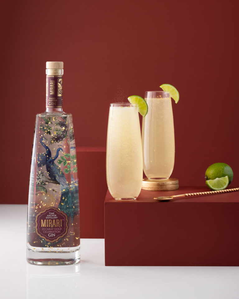 bottle of Mirari celebration gin with ginger lime cocktail