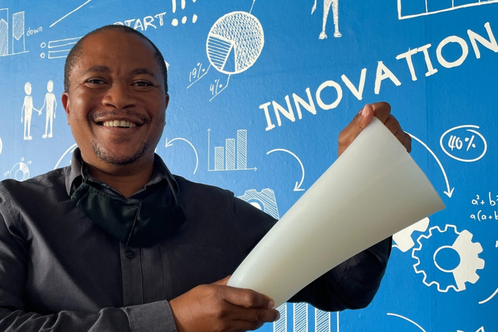 man holding amputees silicone socket liner blue wall in background innovation